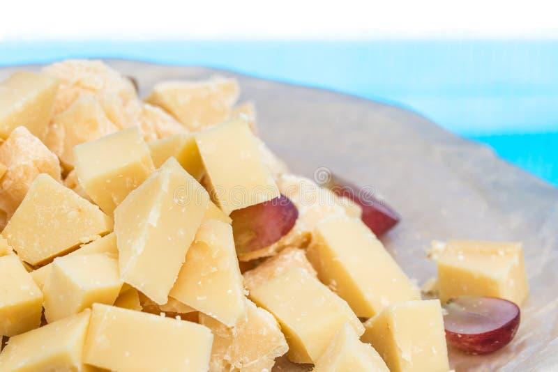 Szczegółowy zakończenie na parmigiano kawałkach z winogronem na drewnianym talerzu fotografia stock