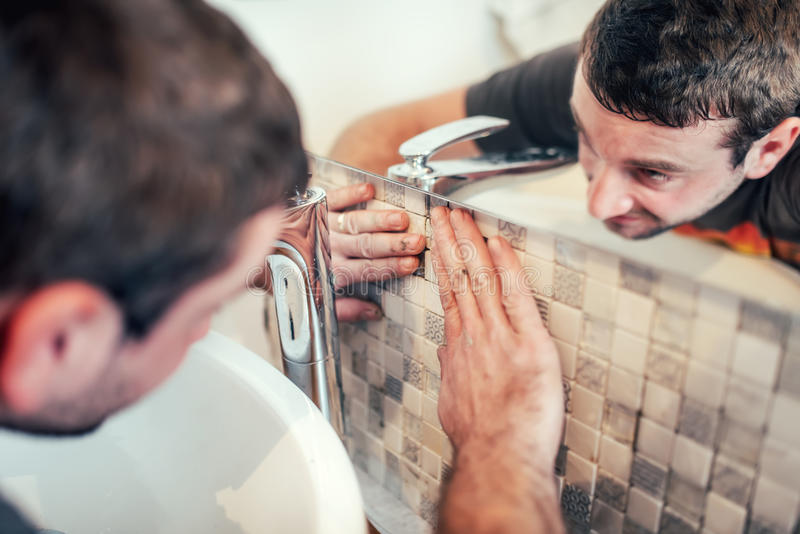 Szczegóły pracownik budowlany Przemysłowy pracownik odnawi mieszkanie i kłaść ceramiczne mozaik płytki w łazience zdjęcia stock