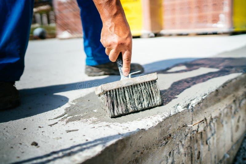 szczegóły pracownik używa muśnięcie dla zakrywać betonową piwnicę z wodoodpornymi materiałami zdjęcia royalty free