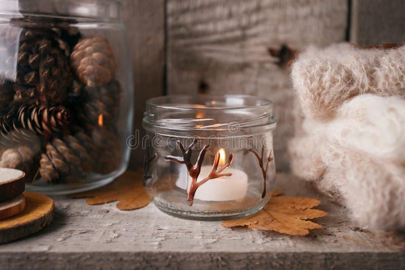 Szczegóły spokojny życie w domowym wewnętrznym żywym pokoju Piękny candlestick, rżnięty drewno, ciepły płótno, słój z pinecones,  obrazy stock