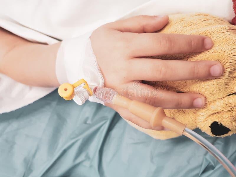 Szczegóły z ręką chora mała dziewczynka w pediatrycznej szpital rezerwie z cannula i trzymać misia, zdjęcie royalty free