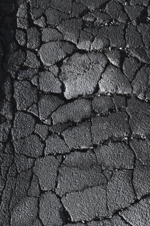 Szczeliny i pęknięcia w asfaltowej ulicznej drodze fotografia royalty free