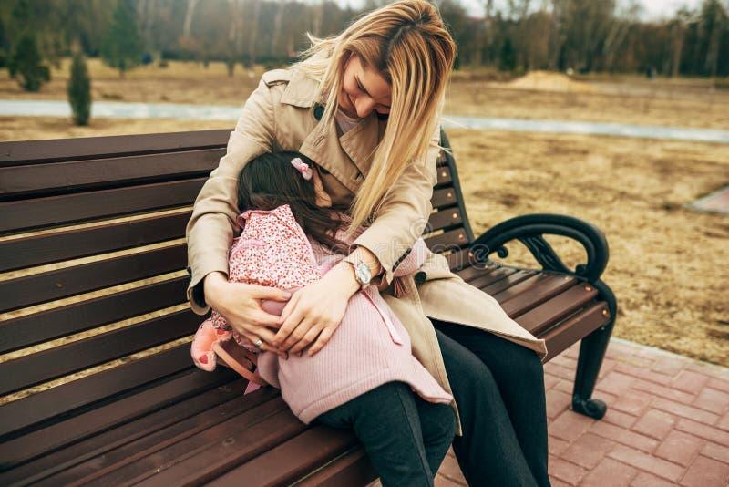 Szczery wizerunek szczęśliwy macierzysty obejmowanie jej dziewczyna dzieciaka obsiadanie na ławce outdoors Kochająca młoda kobiet zdjęcia stock