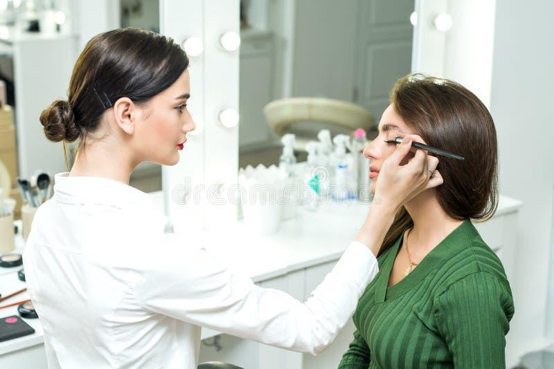 Szczotkarski stosuje beżowy makeup obraz stock