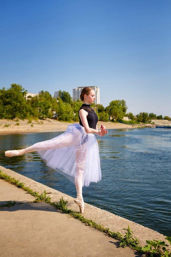 Szczupła balerina w spódniczka baletnicy tanu na riverbank arabesk zdjęcie royalty free