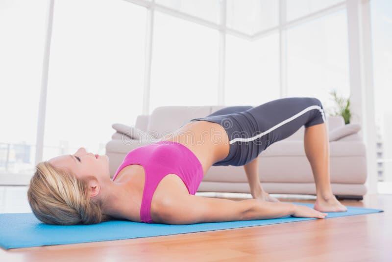 Szczupła blondynka robi pilates na ćwiczenie macie obraz royalty free