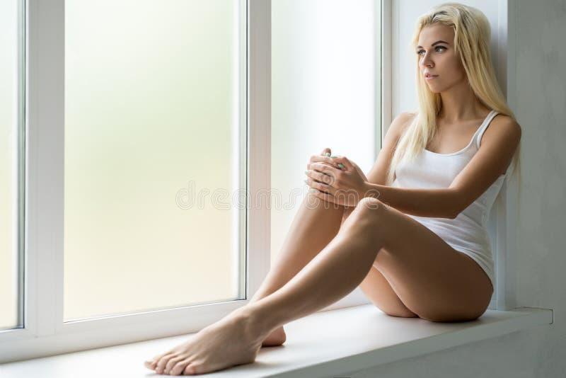 Szczupła blondynka w bielu wierzchołku na nadokiennym parapecie w studiu obrazy stock