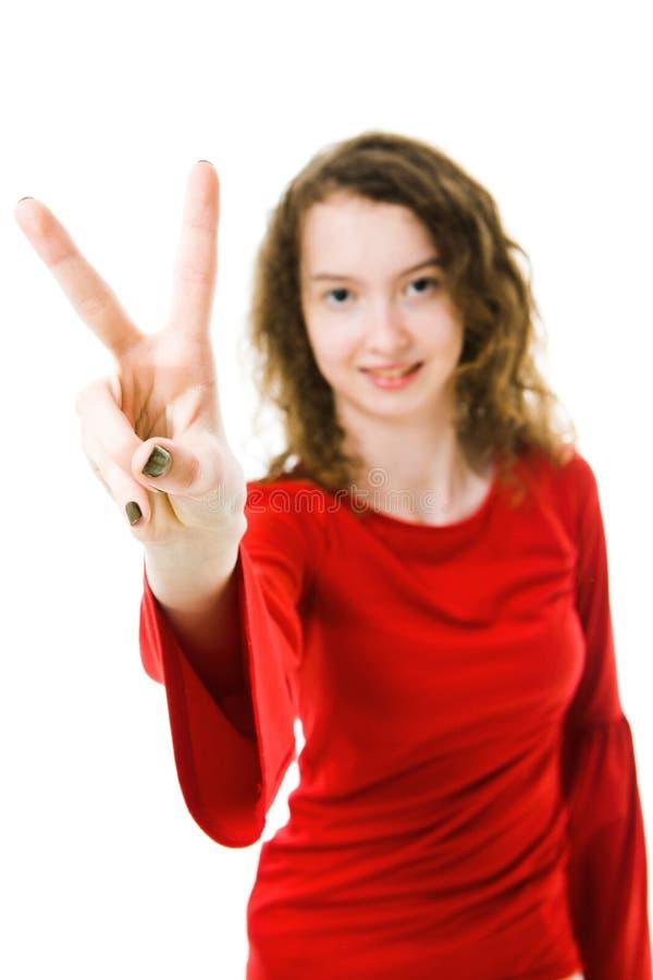 Szczupła dziewczyna w czerwieni zwycięstwa smokingowym pokazuje znaku z dwa palcami obraz stock