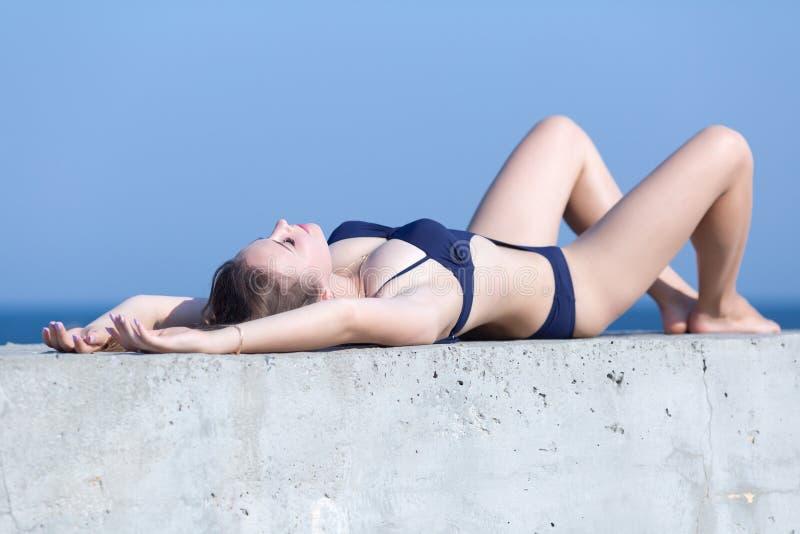 Szczupła dziewczyna w stroju jednoczęściowy swimsuit sunbathes na betonowej ścianie zdjęcia stock