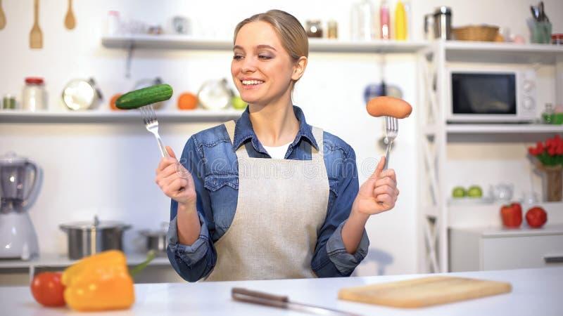 Szczupła dziewczyna wybiera między warzywem i kiełbasą, żywność organiczna vs gmo produkty zdjęcia royalty free