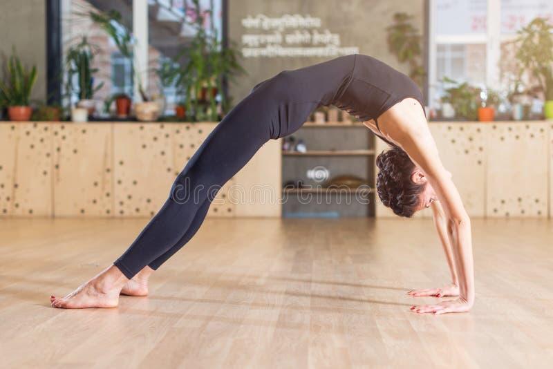 Szczupła elastyczna młoda kobieta robi joga ćwiczenia pozyci w bridżowej pozyci w gym obrazy stock