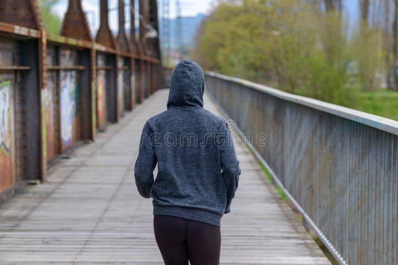 Szczupła kobieta jest ubranym hoodie jogging na moscie obraz stock