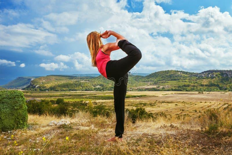 Szczupła kobieta robi królewiątku tana joga poza obraz stock