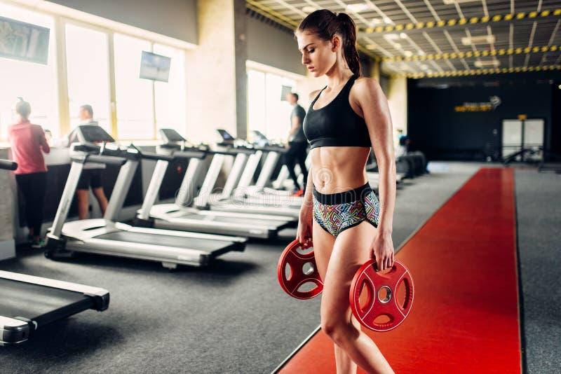 Szczupła kobieta w sportswear chwytów ciężarze w rękach zdjęcia royalty free