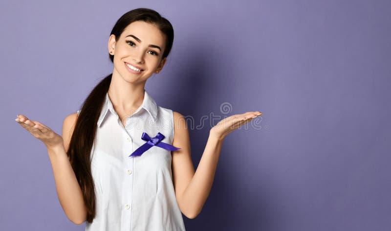 Szczupła kobieta z purpurowym faborkiem światowy epilepsja dzień, nowotworu dnia pozy jakby trzyma coś na otwartych palm rękach obrazy royalty free