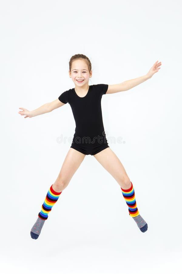 Szczupła nastoletnia dziewczyna robi gimnastykom tanczy w doskakiwaniu na bielu fotografia royalty free
