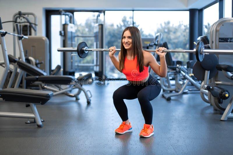 Szczupła przystojna młoda kobieta w sportswear kuca z barbell na ramieniu w gym fotografia royalty free