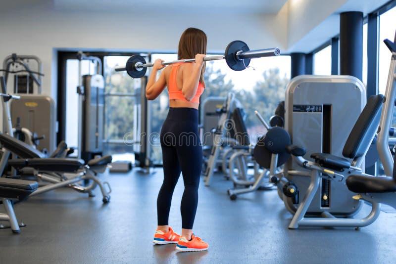Szczupła przystojna młoda kobieta w sportswear kuca z barbell na ramieniu w gym zdjęcia stock