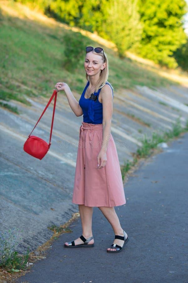 Szczupła wysoka blondynki dziewczyna w błękita wierzchołku, światło - różowa spódnica, czarni sandały, jest ubranym okulary przec obrazy stock