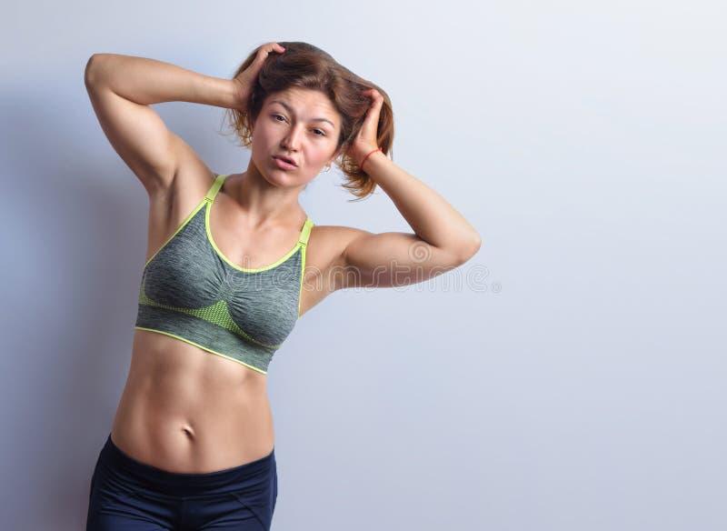 Szczupły żeński sprawność fizyczna trener w popielatym wierzchołku na pracownianym tle obraz stock