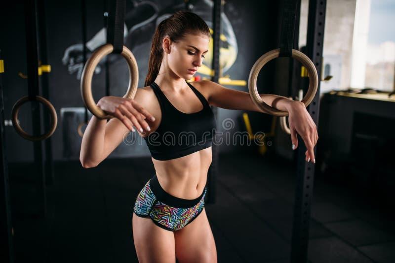 Szczupły żeńskiej atlety ćwiczenie na gimnastycznych pierścionkach zdjęcie stock