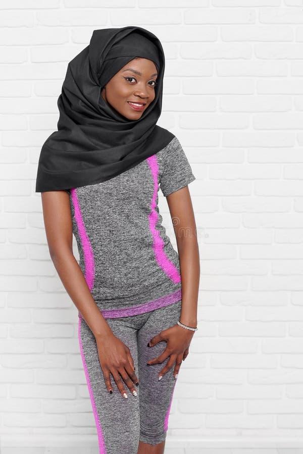 Szczupły afrykanina model w czarnym hijab i popielatym sportswear obraz stock