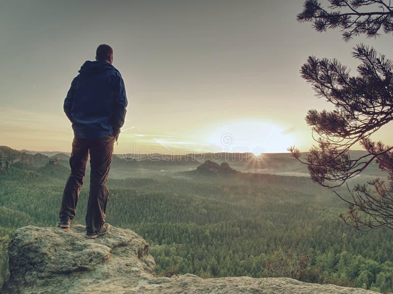 Szczupły facet na szczytowym dopatrywaniu nad doliną powstający słońce obraz royalty free