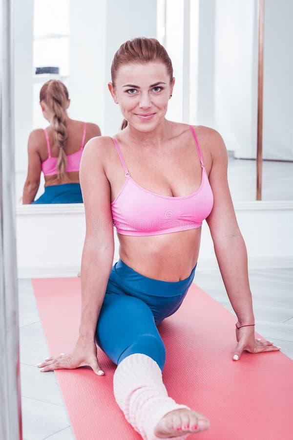 Szczupły sportowy kobiety obsiadanie w stronie rozszczepiającej podczas gdy trenujący w ranku fotografia stock
