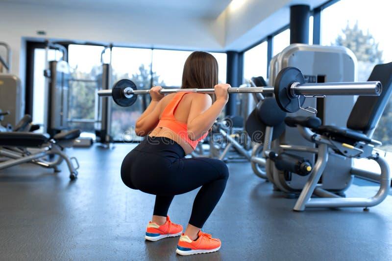 Szczup?a przystojna m?oda kobieta w sportswear kuca z barbell na ramieniu w gym obraz royalty free