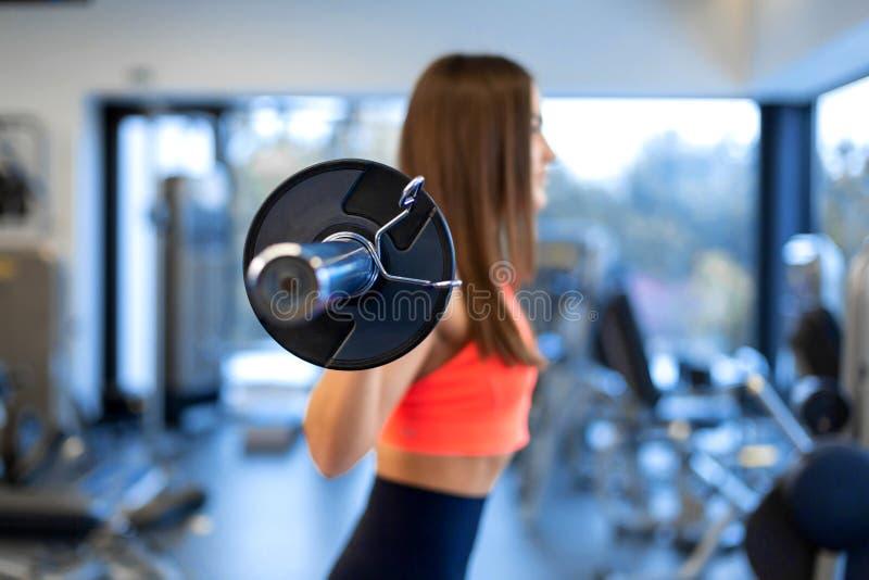 Szczup?a przystojna m?oda kobieta w sportswear kuca z barbell na ramieniu w gym fotografia stock