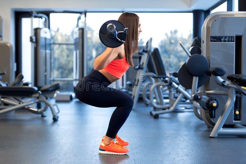 Szczup?a przystojna m?oda kobieta w sportswear kuca z barbell na ramieniu w gym zdjęcie stock