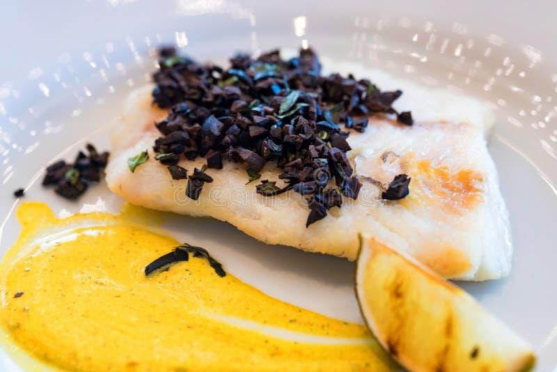 Szczupak żerdź polędwicowa z warzywami i oliwkami na bielu talerzu fotografia stock