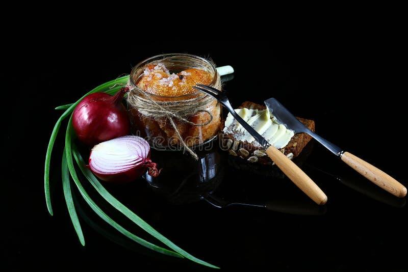 Szczupaka kawior, roe w szklanym słoju, surowi rolni jajka, purpurowa cebula, zielone cebule, chleb z masłem, rozwidlenie i nóż n obrazy stock