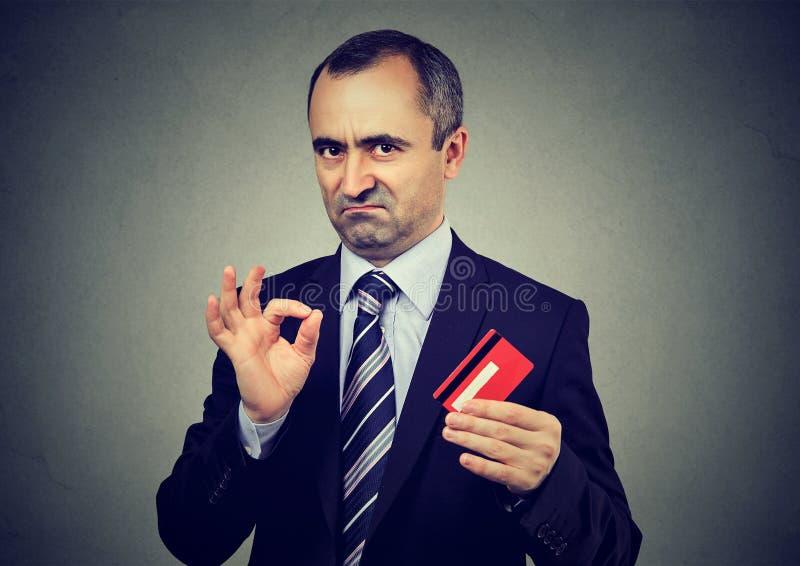 Szczwanej kłamcy biznesmena dojrzały pracownik reasekuruje ich kredytową kartę jest best obraz stock
