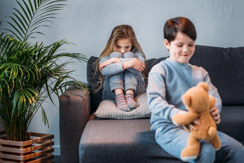 Szczwany chłopiec mienia miś podczas gdy obrażający dziewczyny obsiadanie na kanapie zdjęcie royalty free