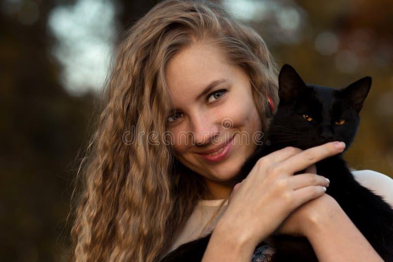 Szczwany, piękny, figlarnie, chytry, chytry, pieści czarnego kota i trzymał Dziewczyny miłości zwierzęta domowe Zwierzę domowe je obrazy royalty free