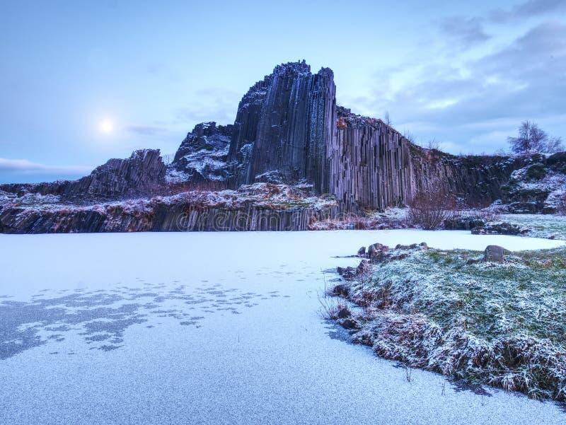 Szczyt bazaltowi filary zakrywający śniegiem, marznący basen Księżyc w pełni w niebieskim niebie w tle fotografia royalty free