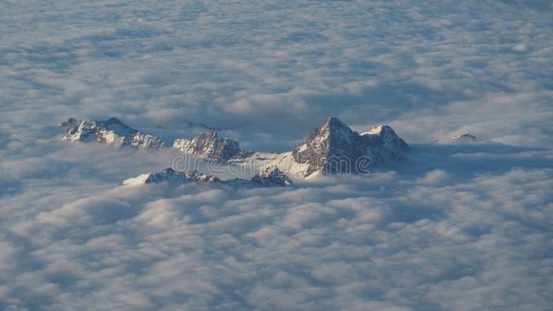 Szczyty góry wzrastają out od chmur które zakrywają ziemię Krajobraz od samolotowego okno zdjęcie royalty free