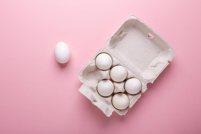 Sześć białych jajek w kartonu pudełku na menchia papieru tła Odgórnego widoku symbolu Szczęśliwym Wielkanocnym mieszkaniu nieatut zdjęcie royalty free