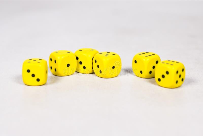 Sześć Żółtych kostek do gry na Czystych Jasnych Białych szarość Siwieją tło Wykładającego Przypadkowo zdjęcia royalty free