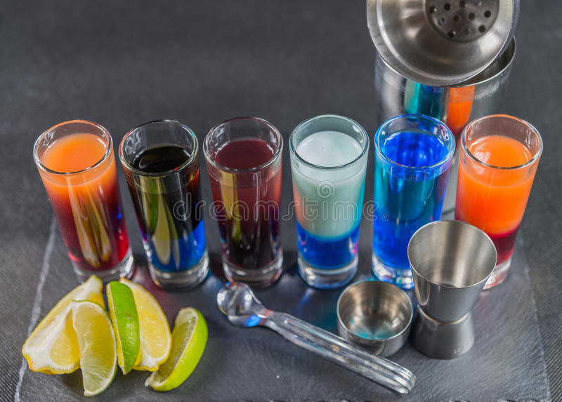 Sześć różnych barwionych strzałów pije, prążkowany up na czarne kamienne śliwki zdjęcia stock
