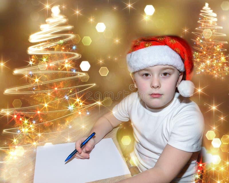 Sześć roczniaków ślicznych chłopiec z czerwonymi bożymi narodzeniami nakrywa pisać liście Święty Mikołaj indoors blisko choinki J fotografia royalty free