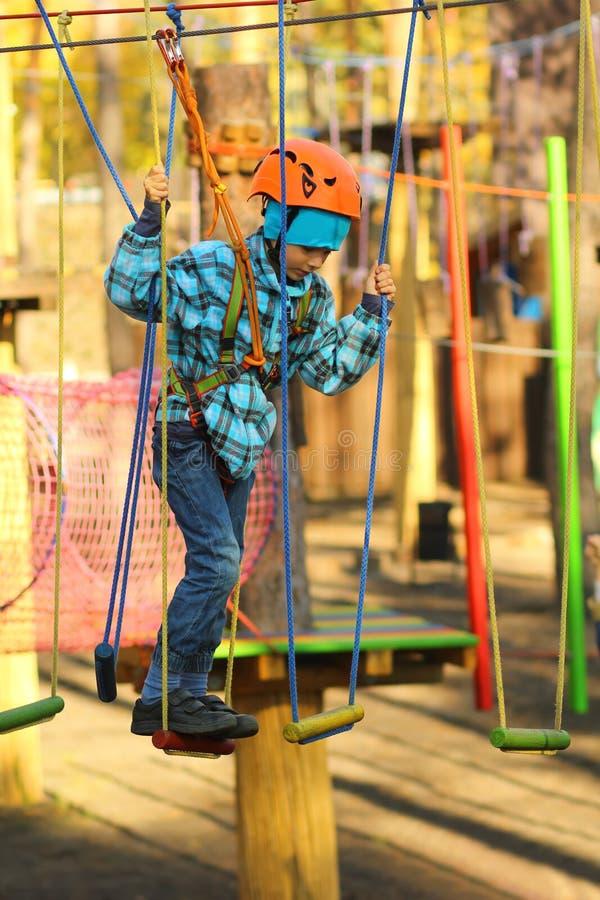 Sześć roczniaków chłopiec surmounting przeszkoda kurs w linowym parku obrazy stock