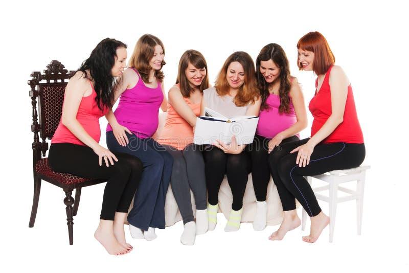 Sześć uśmiechniętych kobieta w ciąży siedzi a i czyta fotografia stock