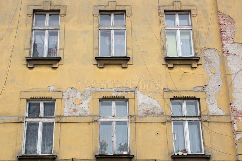 Sześć Windows na fasadzie stary podławy koloru żółtego dom zdjęcia stock