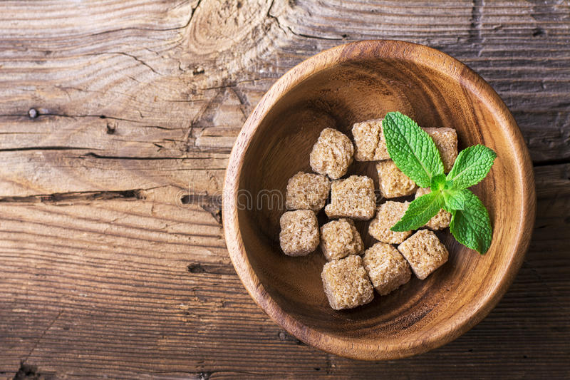 Sześcian trzciny naturalny brown cukier w drewnianym pucharze na tle Pojęcie żywność organiczna Selekcyjna ostrość obraz stock