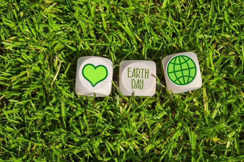 Sześciany i kostki do gry z Ziemskim dniem z zielonymi elektryczność ikonami zdjęcie royalty free