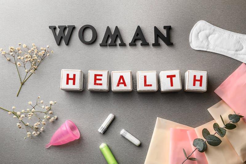 Sześciany komponujący słowa kobieta i zdrowie na popielatym stole obraz royalty free
