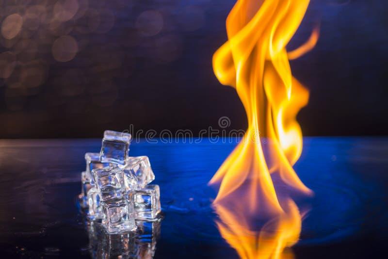 Sześciany lód i ogień na nawadniają powierzchnię na abstrakcjonistycznym tle fotografia stock