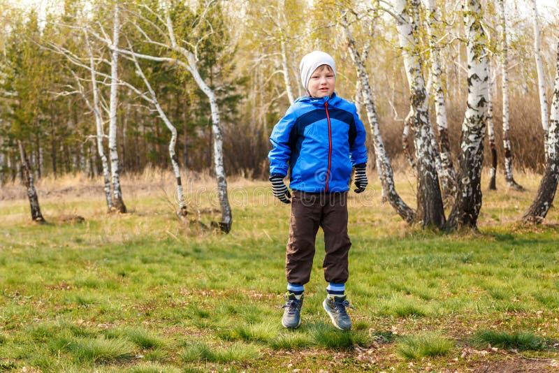 Sześcioletni chłopiec doskakiwanie na zielonej trawie fotografia royalty free